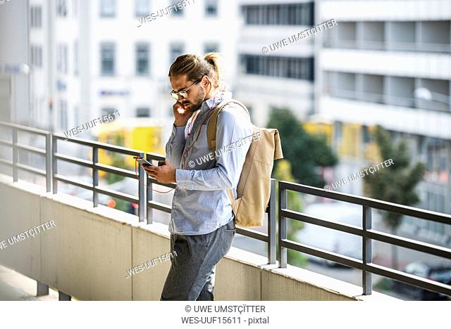 Young businessman with backpack, standing in parking garage, using smartphone