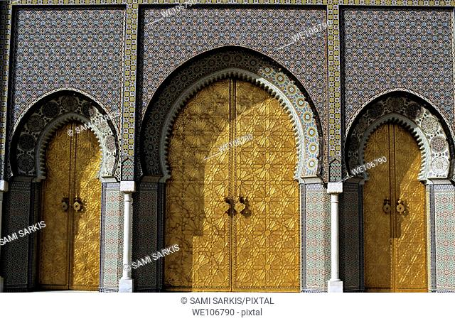 Three golden doors forming the grand entrance to the Royal Palace in Fez, Morocco