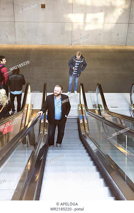 High angle view of business people on escalator at subway station