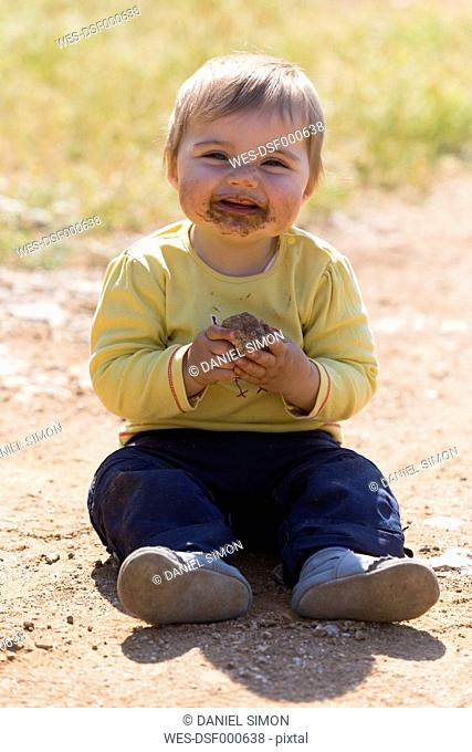 Messy baby playing with mud