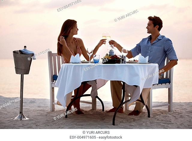 Portrait of an attractive young couple toasting champagne and enjoying dinner in beach