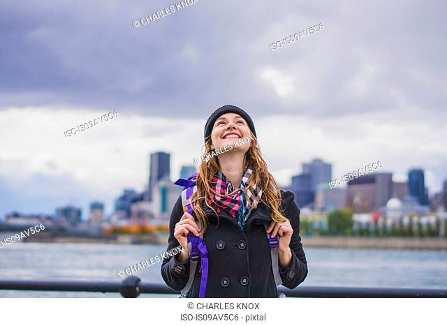 Young woman wearing rucksack, looking up, smiling, Ile Ste-Helene, Montreal, Quebec, Canada
