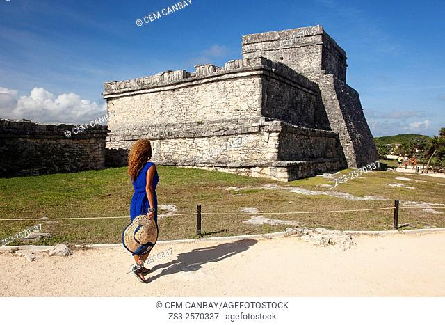 Woman posing in Mayan Ruins at Maya archeological site of Tulum near the Castle-Castillo, Quintana Roo, Yucatan Province, Mexico, Central America