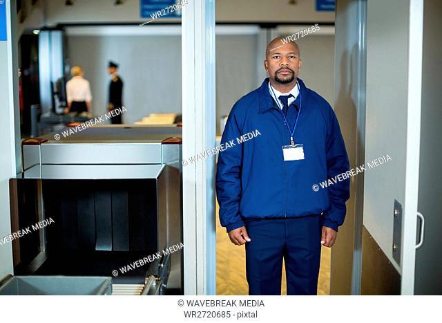 Airport security officer standing in metal detector door