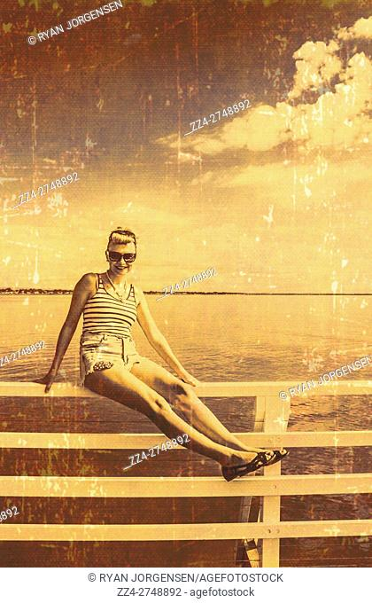 Cute 1960 style poster portrait of a faded pinup girl posing carefree in summer fashion on a jetty rail. Weathered marina pin-ups (taken Shorncliffe Pier, QLD