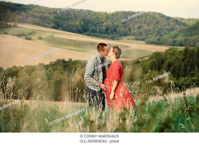Romantic pregnant mid adult couple kissing in field