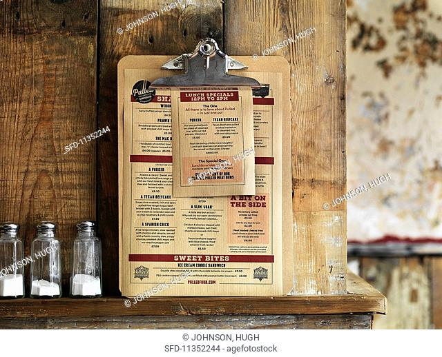 A menu consisting of pulled pork dishes leaning against a rustic wooden wall (USA)