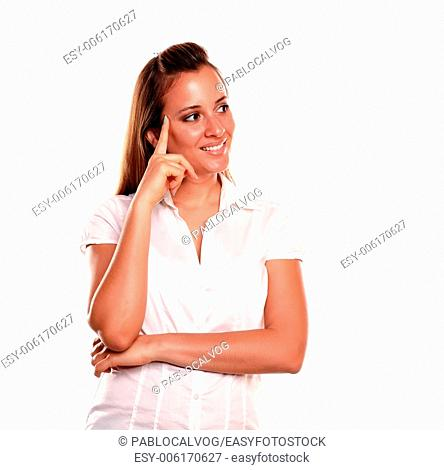Stylish reflective young woman looking to her left against white background - copyspace