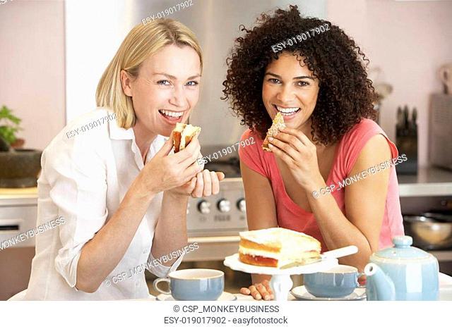 Female Friends Enjoying Tea And Cake At Home