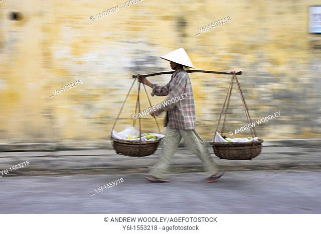 Conical hat woman with banana baskets walks from market Hoi An historic town mid Vietnam