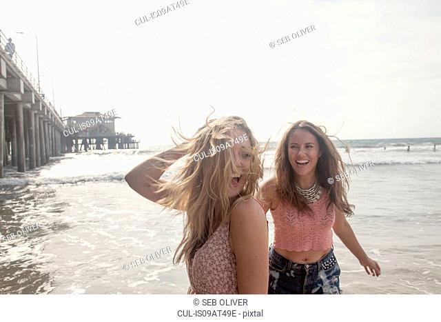 Two young women having fun on windswept beach, Santa Monica, California, USA