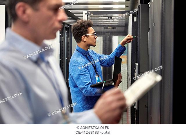 Male IT technicians with clipboard and laptop working at panels in server room