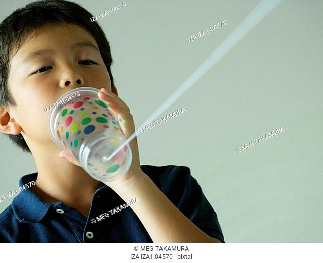 Close-up of a boy using a tin can phone