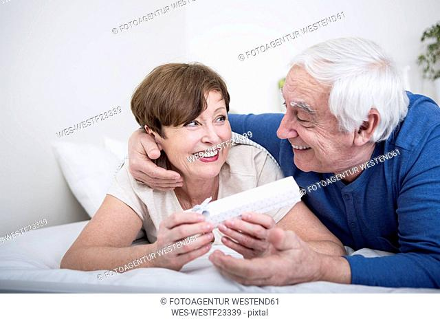 Senior couple lying in bed, man giving present to woman