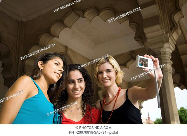 Close-up of a young woman standing with her friends and taking a picture of themselves, Taj Mahal, Agra, Uttar Pradesh, India