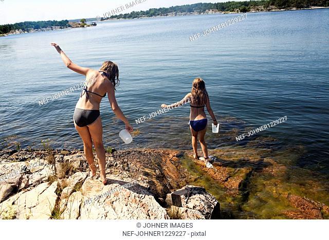 Two girls in bikinis entering lake