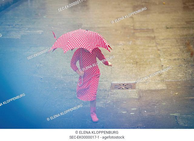 Girl (10-12) with umbrella walking in rain