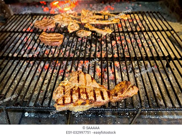 T-Bone steak on grill and fire, shallow depth of field