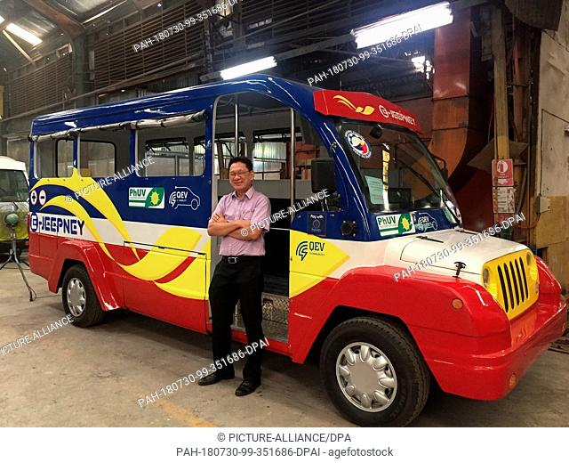 03 July 2018, Philippines, Manila: Roberto Cruz, Deputy Managing Director of PHUV Incorporated, stands in front of an electrically powered Jeepney van