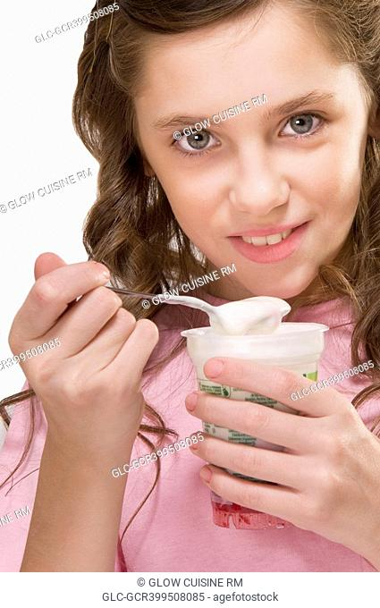 Portrait of a girl eating a cup of yoghurt