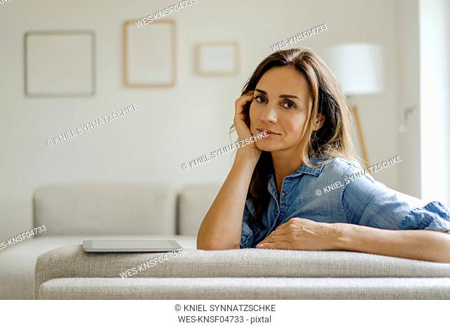 Portrait of mature woman resting on couch at home