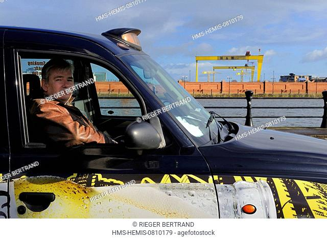 United Kingdom, Northern Ireland, Belfast, Billy Scott in his Black Cab in front of the Samson and Goliath gantry cranes from Harland and Wolff that have become...