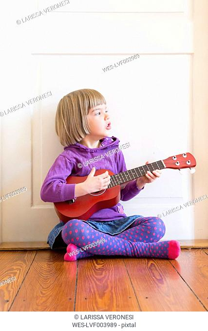 Portrait of little girl sitting on wooden floor playing ukulele