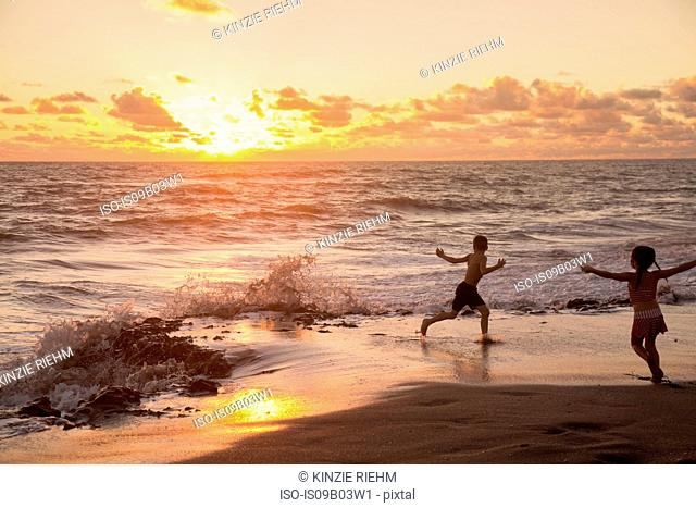 Girl and brother running on beach at sunrise, Blowing Rocks Preserve, Jupiter Island, Florida, USA