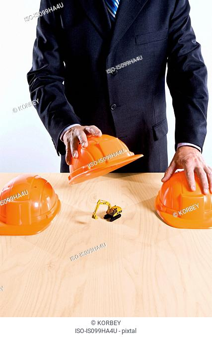 Businessman covering toy digger with hard hat