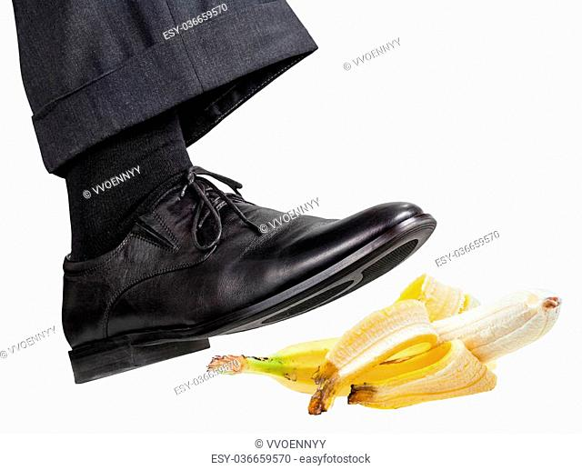 male foot in the right black shoe slips on a banana peel isolated on white background