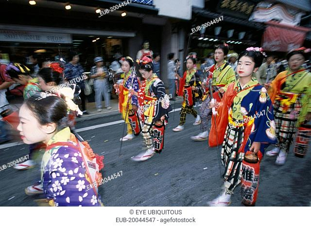 Festival procession with young girls wearing traditional kimonos during the July Gion Matsuri