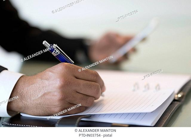 Businessman taking notes in book