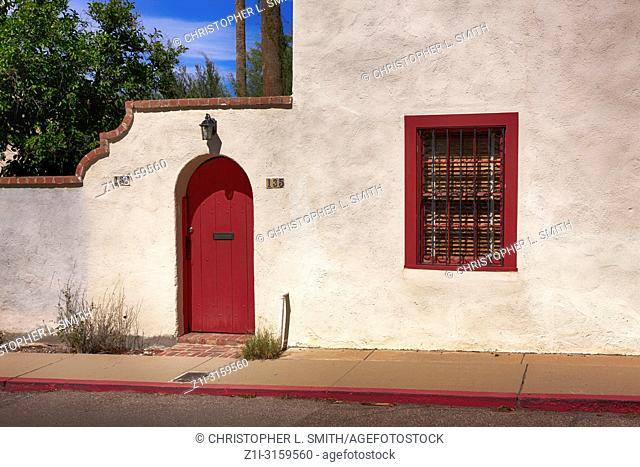 Red door and window frame of an artisan style house in Old Town Tucson City, AZ