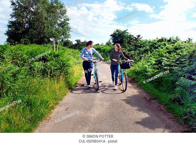 Two young adults pushing bicycles along country lane