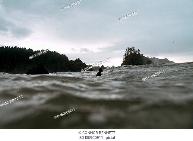 Young male surfer in cold pacific ocean, surface level view, Arcata, California, United States