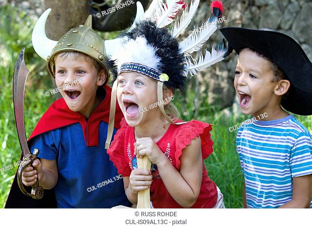 Three children wearing fancy dress costumes, playing in park