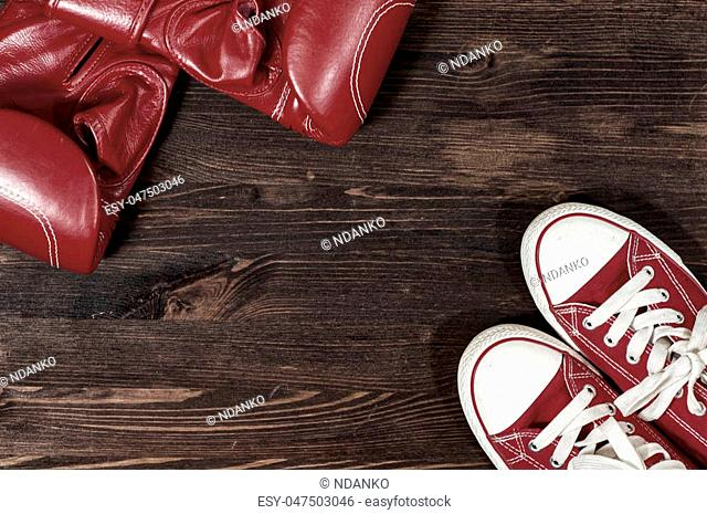 Red boxing gloves and red sneakers on a wooden surface, empty space in the middle