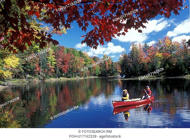 canoeing, canoe, Vermont, VT, Mother and daughter paddle a red canoe on the calm water of Green River Reservoir in Hyde Park in the fall