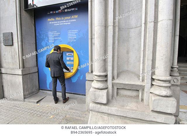 Man using ATM machine, Barcelona, Catalonia, Spain