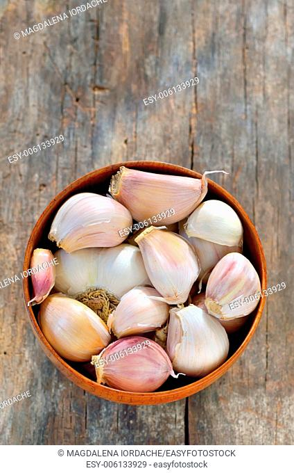 garlic in a wooden bowl isolated on old background
