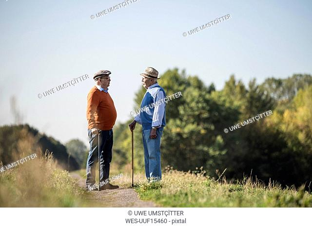 Two old friends standing in the fields, talking about old times