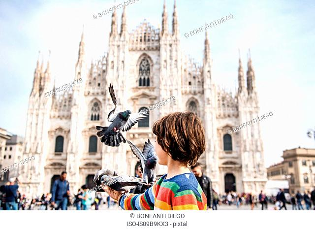 Boy feeding pigeons in Milan Cathedral square, Milan, Lombardy, Italy