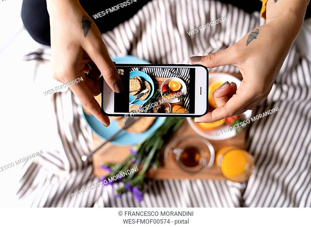 Woman sitting on bed, taking smartphone pictures of her haelthy breakfast