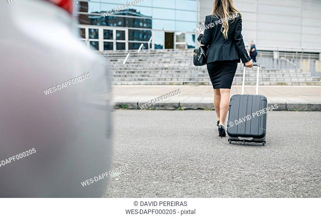 Businesswoman with suitcase on the move