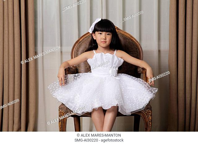 Young girl dressed up in white dress and sitting on nice chair