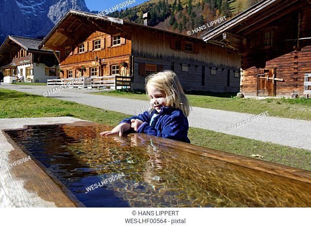 Austria, Tyrol, Eng, small girl bathing hand in drinking trough