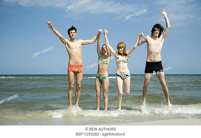Group of friends jumping in water on the beach holding each others hands