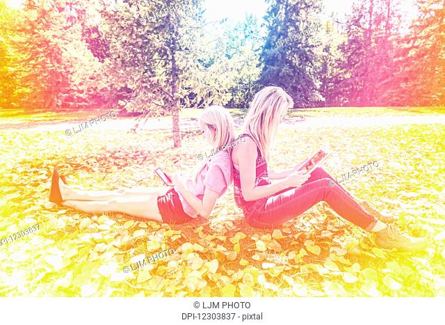 Two sisters having fun outdoors in a city park in autumn looking at social media on their smart phone and tablet; Edmonton, Alberta, Canada