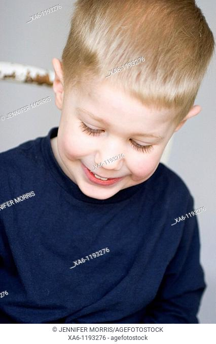 A young child smiling and looking down