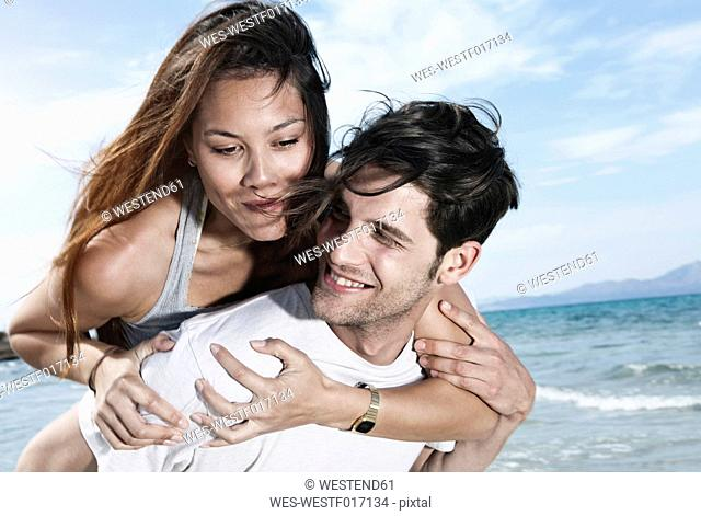 Spain, Majorca, Young man carrying woman on back at beach